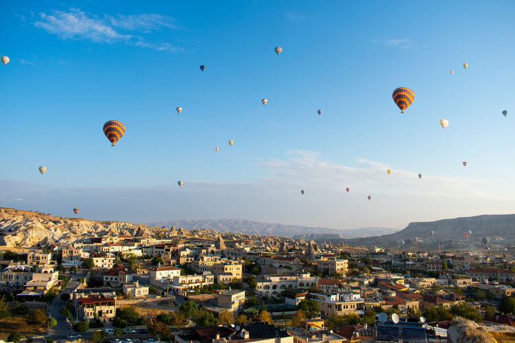 Hot air balloons flying in city against sky
