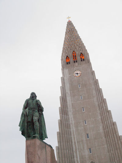 The statue of explorer Leif Ericsson. Hallgrímskirkja is a Lutheran (Church of Iceland) parish church in Reykjavík, Iceland. At 73 metres (244 ft), it is the largest church in Iceland and among the tallest structures in Iceland. The church is named after the Icelandic poet and clergyman Hallgrímur Pétursson (1614 to 1674), author of the Passion Hymns.Situated in the centre of Reykjavík, it is one of the city's best-known landmarks and is visible throughout the city. State Architect Guðjón Samúelsson's design of the church was commissioned in 1937. He is said to have designed it to resemble the basalt lava flows of Iceland's landscape. The design is similar in style to the expressionist architecture of Grundtvig's Church of Copenhagen, Denmark, completed in 1940. Leif Eriksson Reykjavik Clock Clock Tower Day Flag Hallgrìmskirkja Hallgrímur Pétursson Iceland Memories Low Angle View Men Outdoors Patriotism People Tourism Tourist Attraction  Tower Travel Vivid International