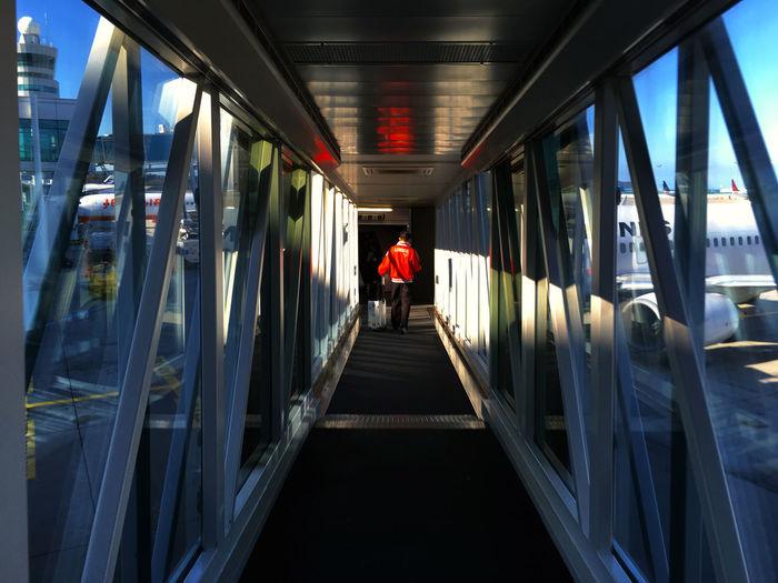 Man walking on passenger boarding bridge at airport runway