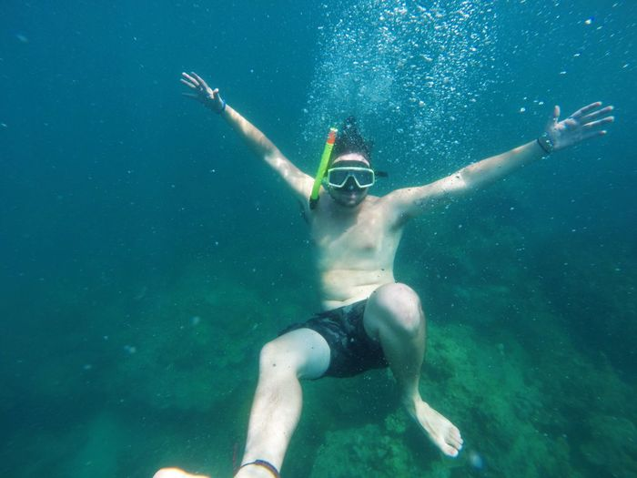 Shirtless Man With Arms Outstretched Snorkeling In Sea