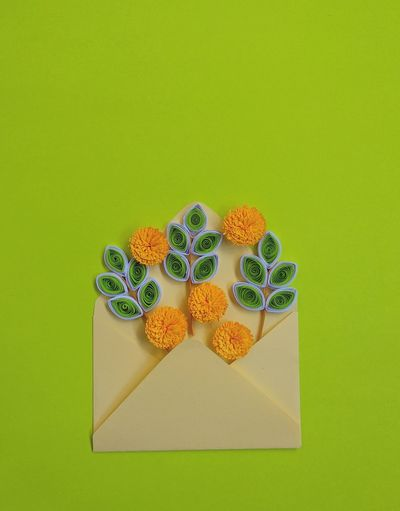 Handmade paper quilling flowers in yellow envelope with green background