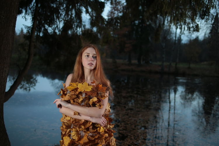 Woman wearing dress made of autumn leaves while standing against lake at dusk