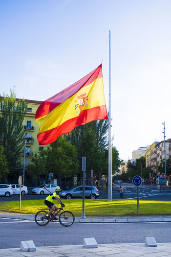 Flags on road against sky in city