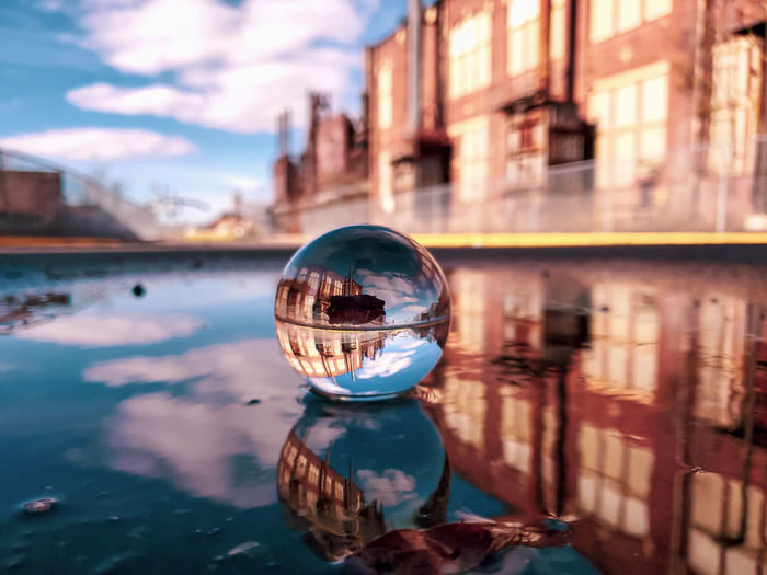 Surface level of crystal ball in water against building