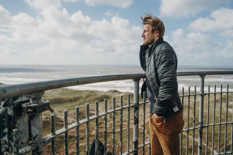 Man standing on top of a lighthouse in Denmark One Person Water Sky Sea Casual Clothing Railing Standing Cloud - Sky Side View Horizon Nature Leisure Activity Horizon Over Water Day Adult Men Young Adult Looking At View Outdoors Contemplation Lighthouse Denmark North Sea Dune