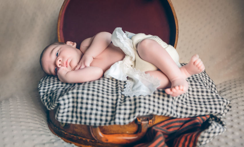 Adorable newborn baby resting lying over a plaid blanket on top of a vintage travel suitcase Baby Horizontal Newborn Blue Eyes Infant Cute Adorable Littel Caucasian Innocence Child Small Innocent person Love Son Human Face Happy Life Relax Childhood Born Skin Body Care Lifestyle New Blanket One Person Family Real People Resting Sleeping Dreaming Dreams Lying Plaid Vintage Travel Suitcases Suitcase Soft Softness Indoors  Bed Babyhood Relaxation Toddler  Full Length Emotion