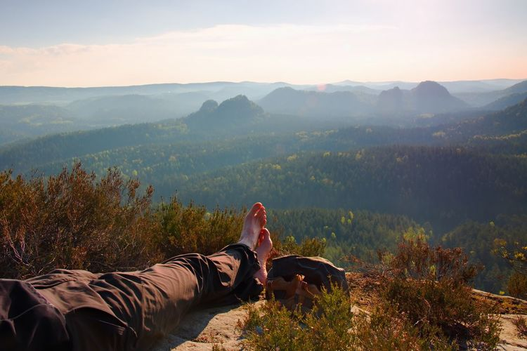 Long tired male legs in hiking trousers take a rest on peak of rock above valley.