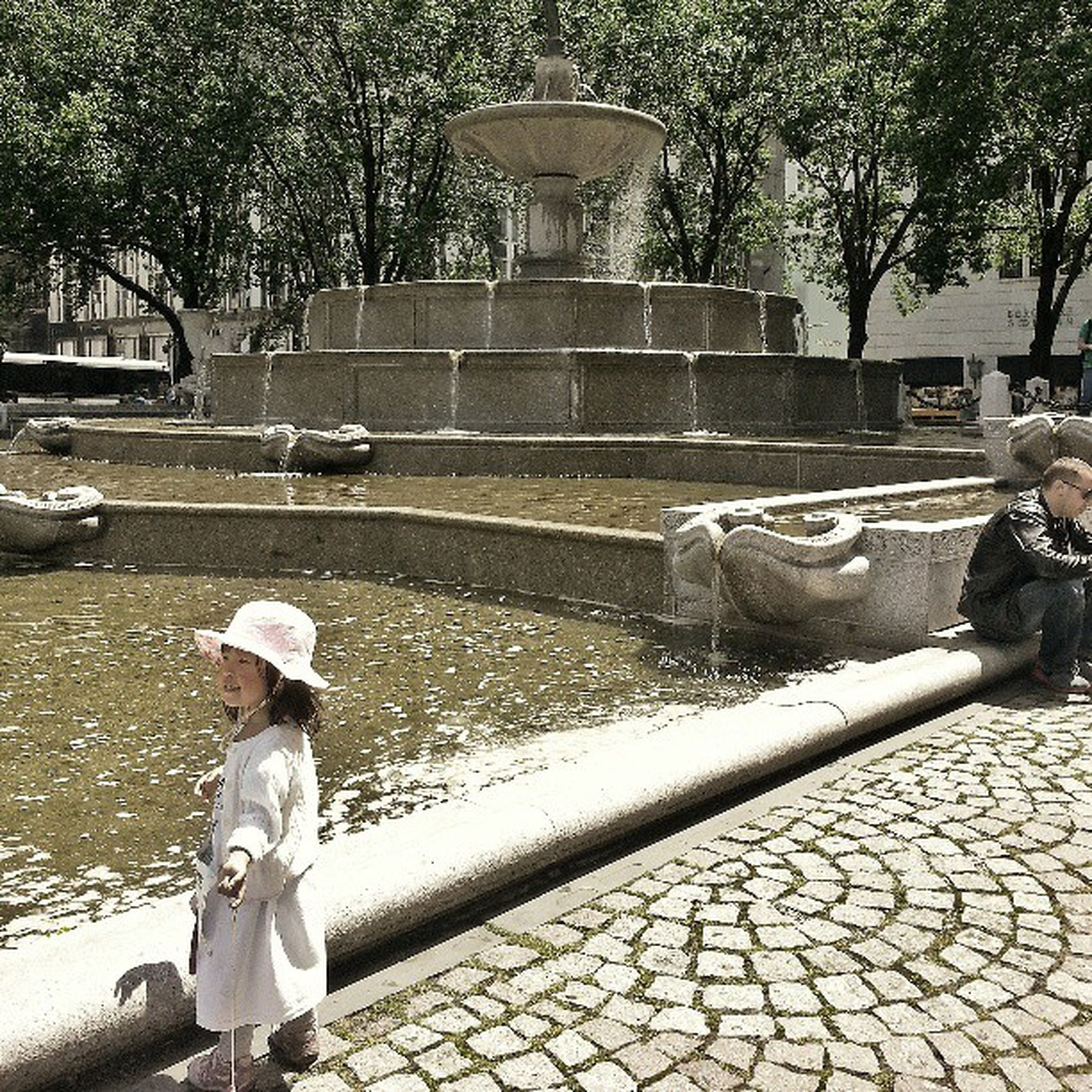 tree, street, cobblestone, transportation, fountain, park - man made space, outdoors, lifestyles, incidental people, sidewalk, day, men, footpath, statue, built structure, full length, car, land vehicle