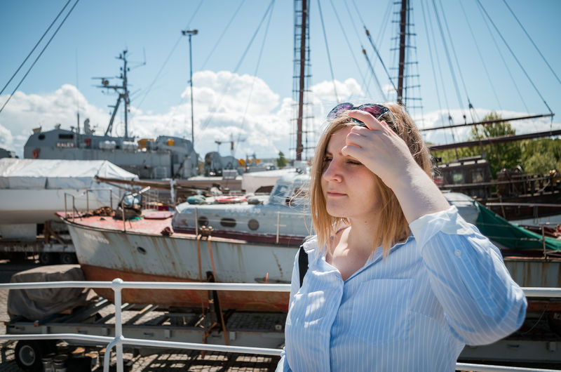 A blonde girl posing in the harbor with navy speedboats in the background. Harbor Merepäevad Sailing Ship Sunny Tallinn Tallinna Merepäevad Casual Clothing Harbor Lennusadam Lifestyles Marine Marine Life Mast Nautical Vessel One Person Outdoors Sky Standing Summer Sunglasses Transportation Vessels Vessels In Port Young Adult Young Woman