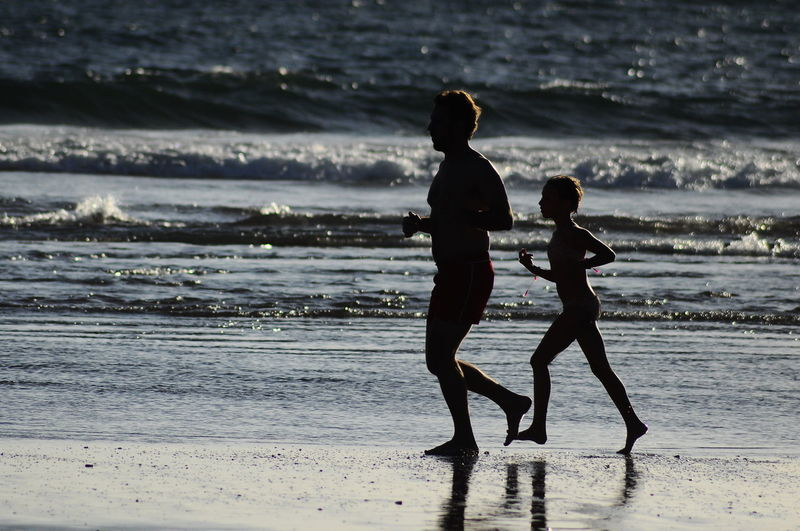 Father and son running on shore at beach