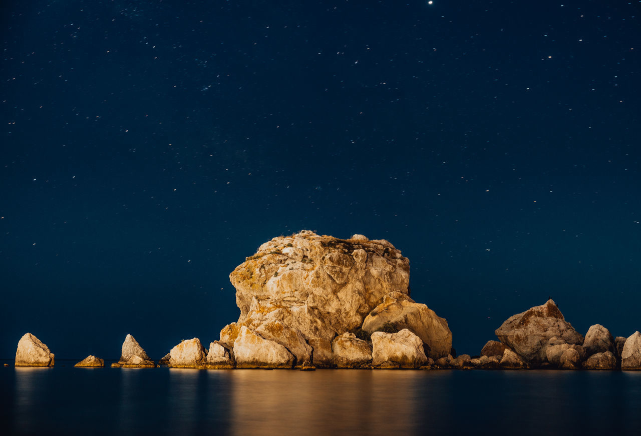 Rock formation in sea against sky at night