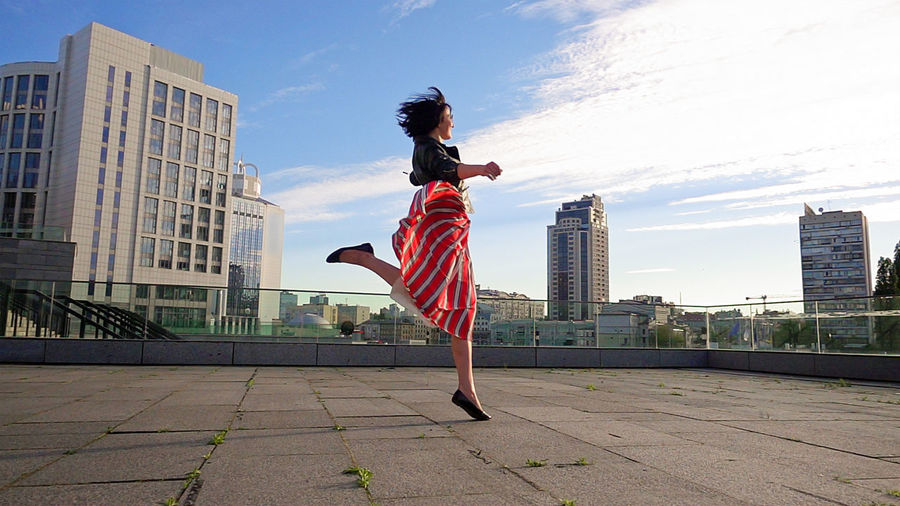 Rear view of woman jumping in city against sky