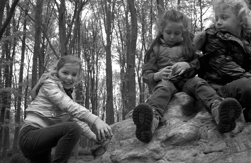 Cute Siblings On Rock In Forest During Winter