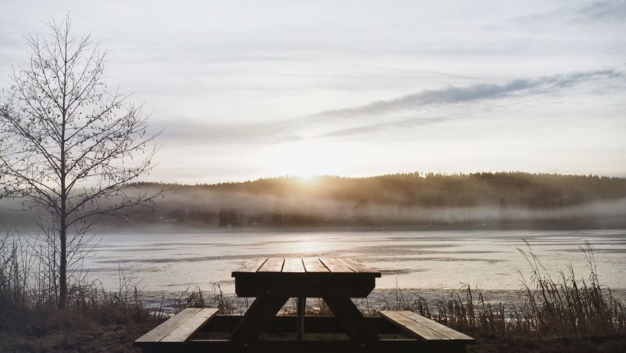 Bench and table on field by lake against sky during sunset in foggy weather