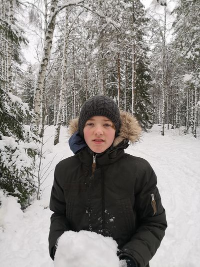 Portrait Of Boy Holding Snow Against Trees In Forest