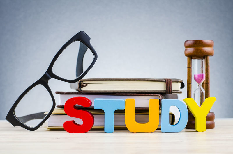 Education and time management concept, word STUDY over hourglass, and spectacles on stacking book Still Life Text Communication Indoors  No People Capital Letter Western Script Studio Shot Close-up Table Multi Colored Letter Alphabet Toy Education Design Gray Background Eyeglasses  Wood - Material