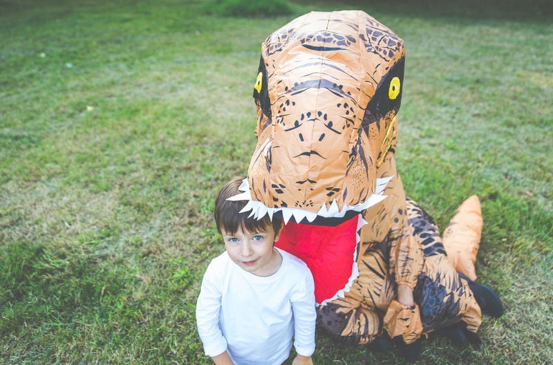 Portrait of boy standing with person wearing dinosaur costume in park