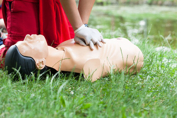 Midsection of paramedic practicing on cpr dummy at grassy field