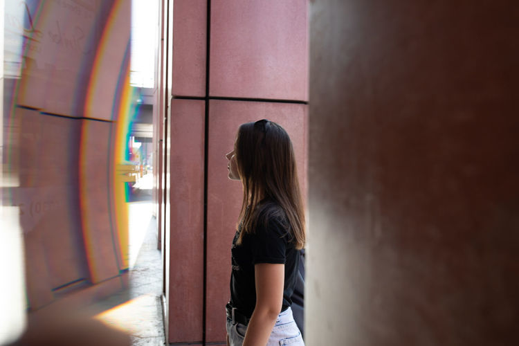Side view of woman standing against wall