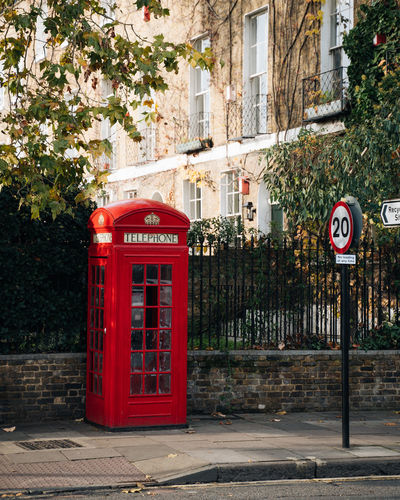 Red telephone booth on sidewalk in city