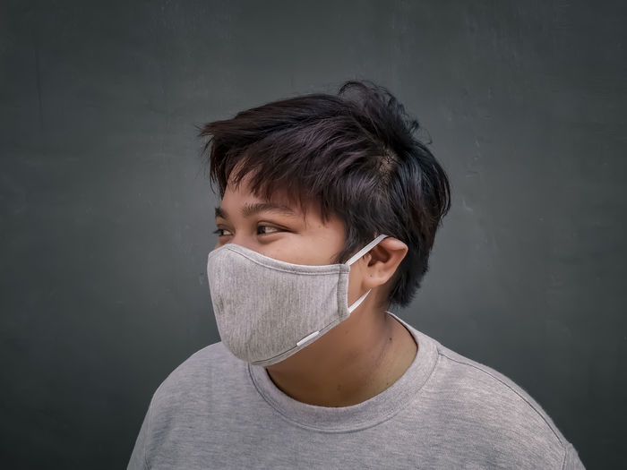 Portrait of girl against wall use mask