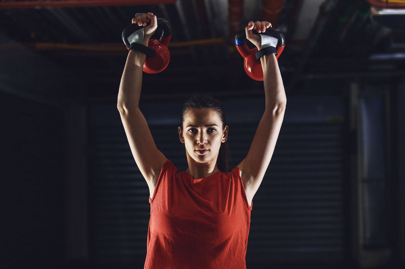 Waist Up Portrait Of Young Woman With Arms Raised Holding Kettlebells