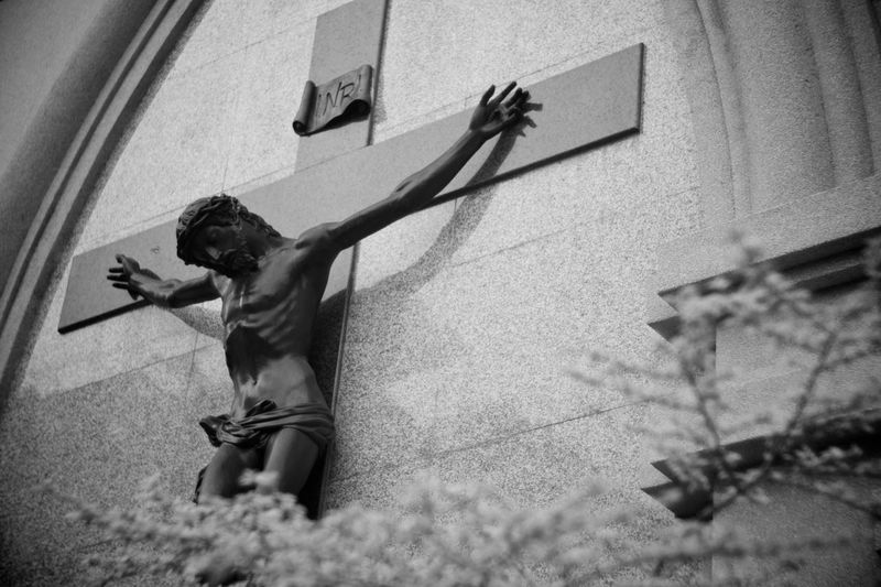Low angle view of jesus christ statue with cross on wall