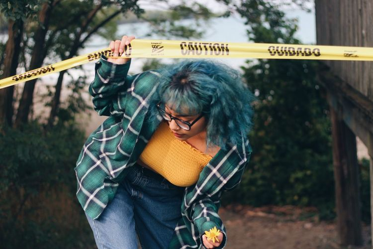 Young woman crossing barricade tape outdoors
