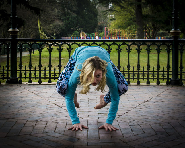 Young woman exercising in gazebo at park