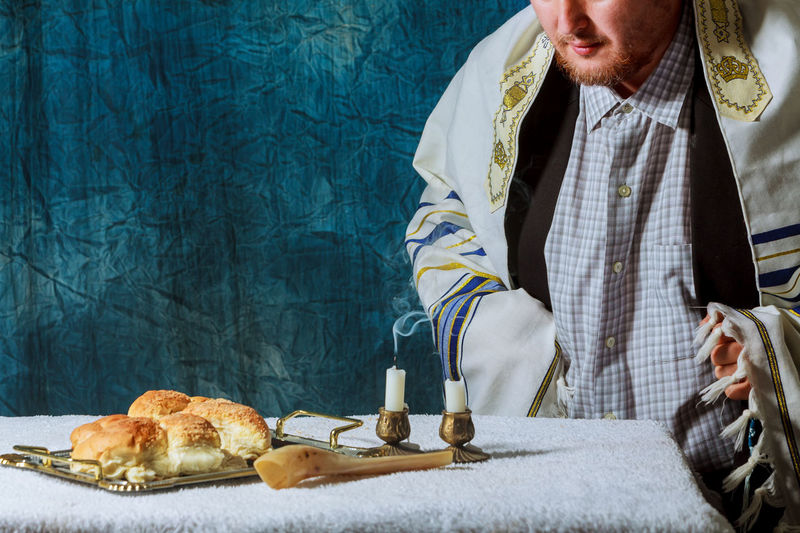 Man Sitting At Breads In Plate By Lit Candles