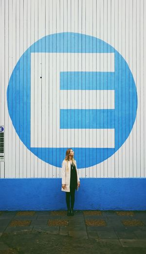 Woman Standing By Letter E On Wall