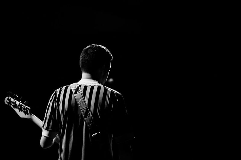 Rear view of man playing guitar against black background