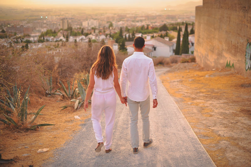 Rear view of couple walking on road during sunset