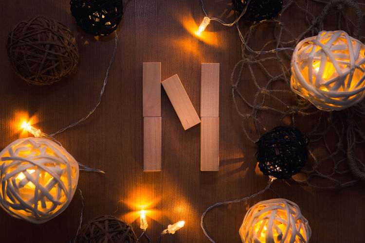 Directly above shot of letter n blocks and illuminated lights on wooden table