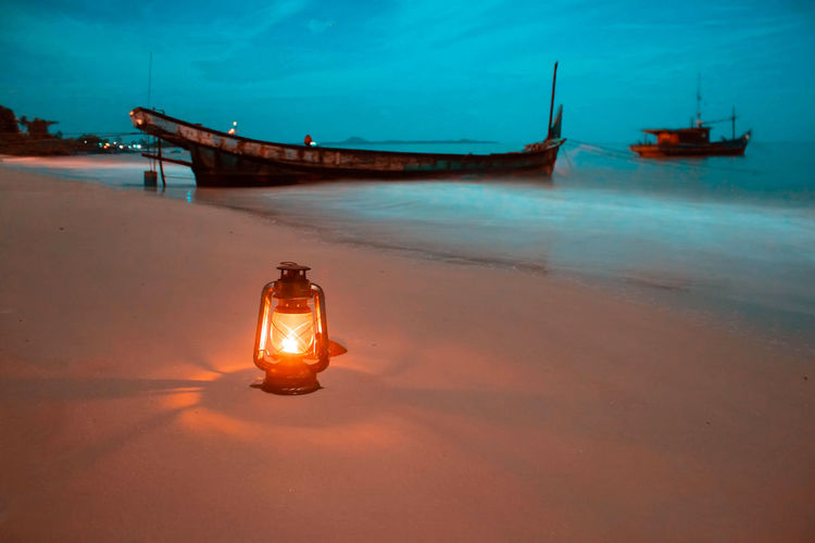 Boat moored on beach against sky during the night with lamp
