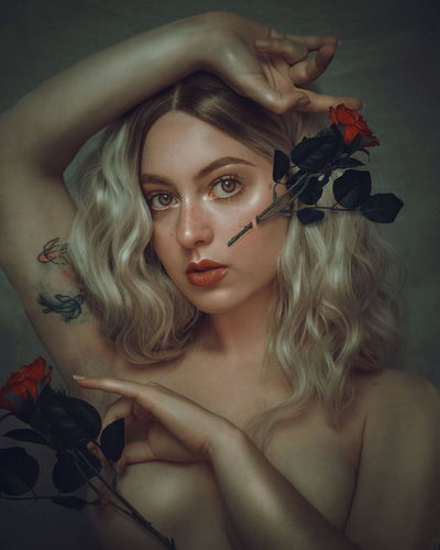 Portrait of beautiful woman with red flower