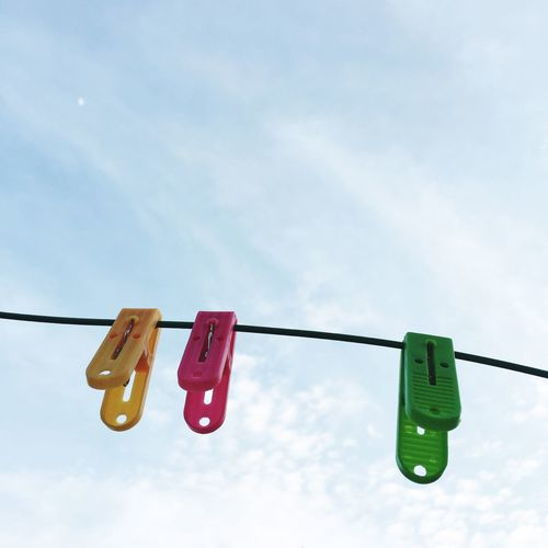 Low angle view of clothespins hanging on clothesline against sky
