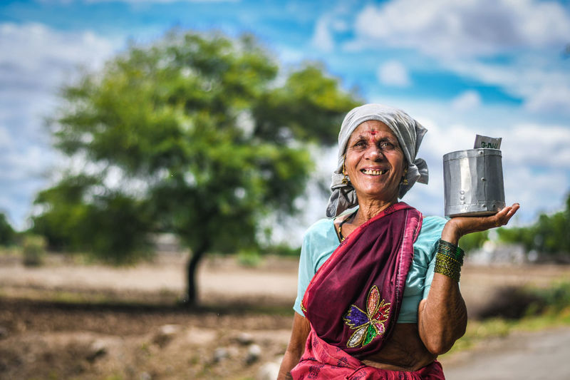 Portrait Of Smiling Woman Farmer Holding Container While Standing Outdoors
