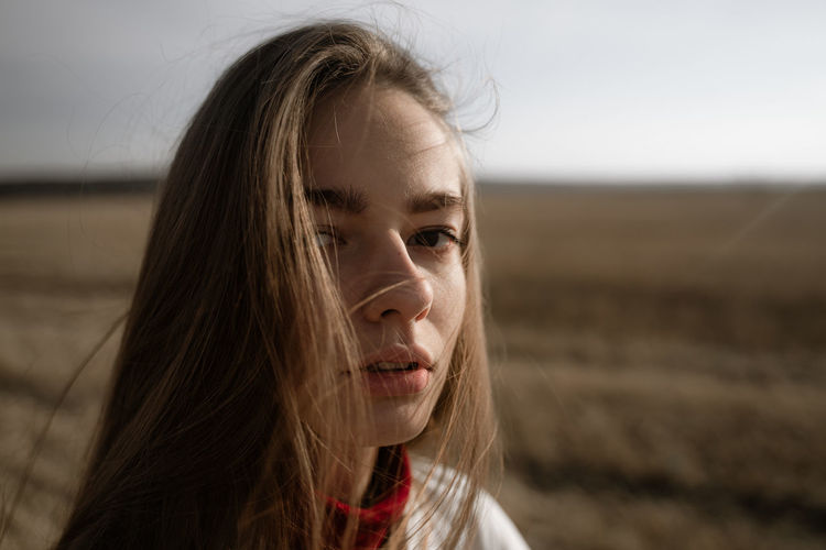 Close-up portrait of young woman standing on field