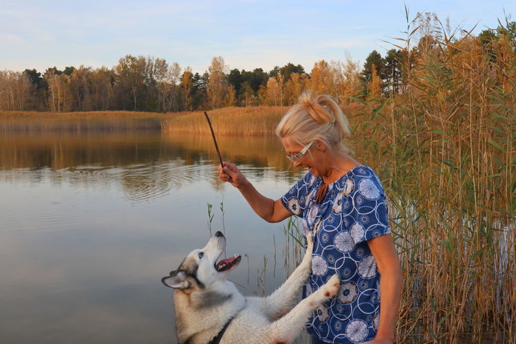 Senior woman playing with dog against lake
