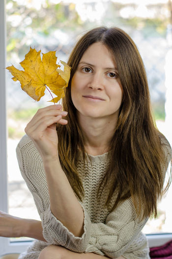 Portrait of young woman holding autumn leaf