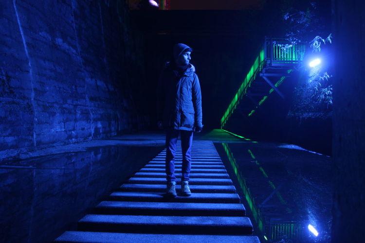 Man standing on illuminated footbridge at night