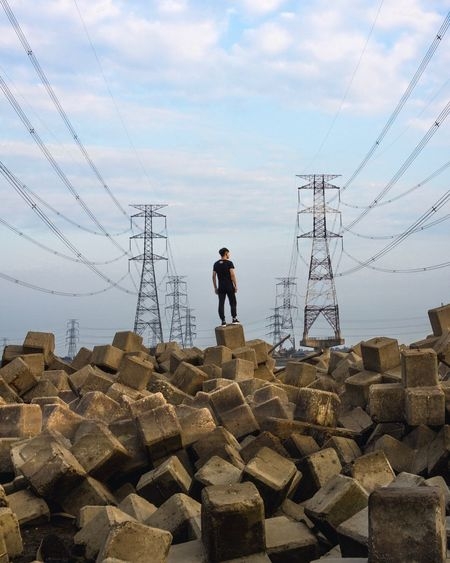 Rear View Of Man Standing On Tetrapod Against Electricity Pylons