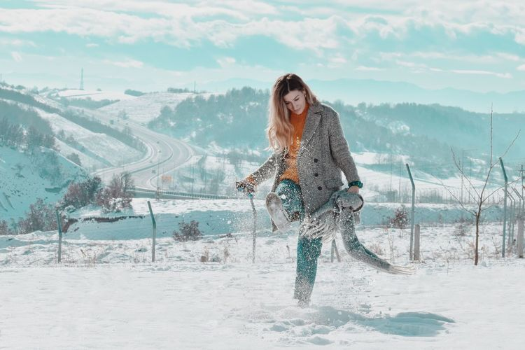 Road Snow Nature Beauty In Nature Tranquility Tranquil Scene Travel Destinations Scenics Scenics - Nature Beauty Beautiful Beautiful Woman Real People Outdoors Day Sunlight Light And Shadow White Background White Color Warm Clothing Mountain Cloud - Sky Full Length Blue Young Women Women Beauty Winter Activity Sky
