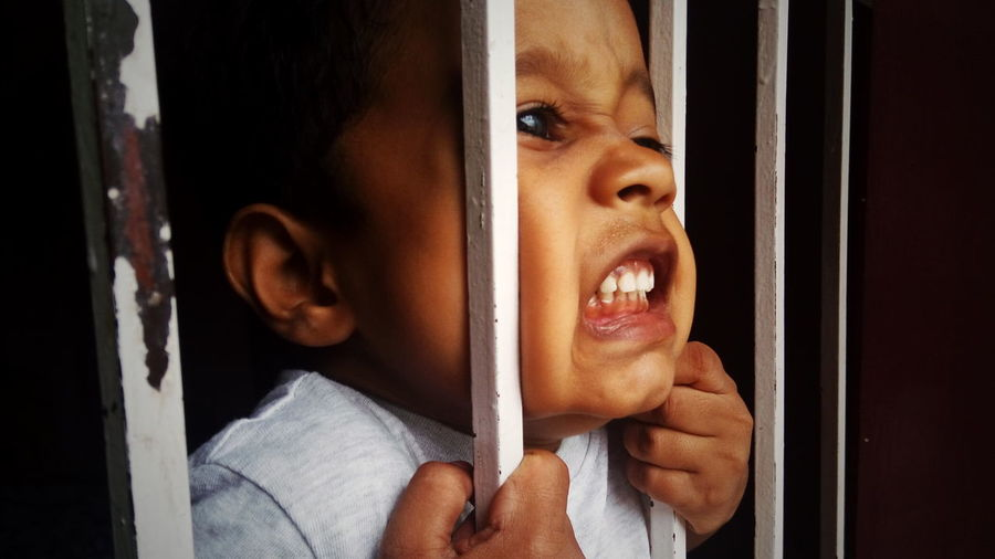 Close-up of aggressive boy holding security bars of window