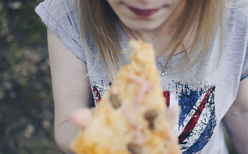 Midsection of young woman eating pizza while standing outdoors