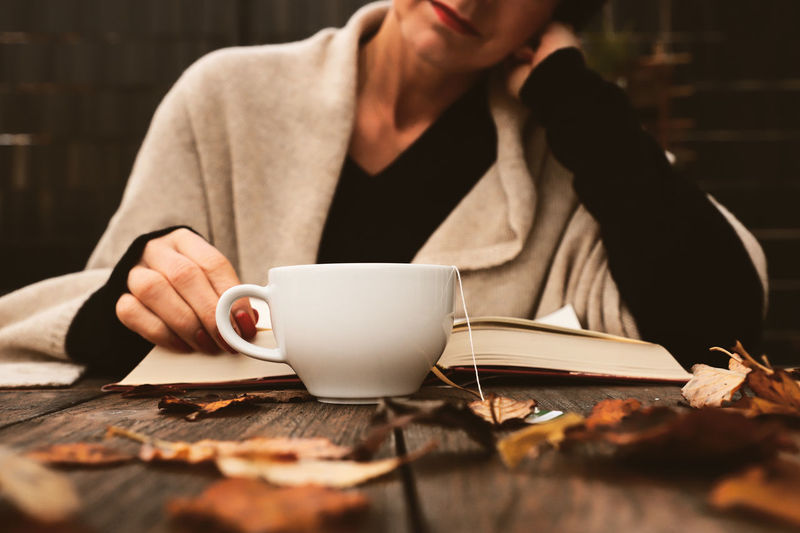 Autumn Mood Reading Cup Tea Hot Drink Drink Relaxing Wooden Table Book Reading A Book Education Fashion Warm Clothing Real People Women Woman Drinking Leaves Autumn Outdoors Focus On Foreground Paper Scarf Cold Temperature Cold Days The Modern Professional Holiday Moments
