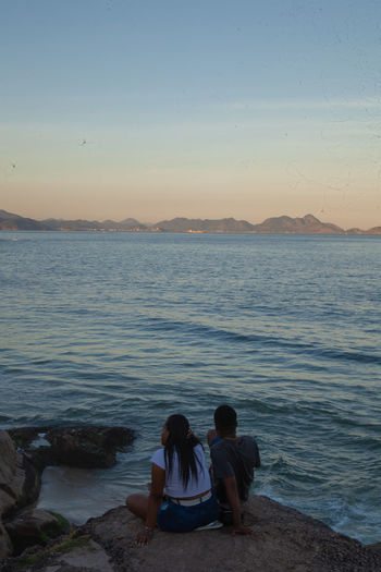 Rear view of couple sitting on beach against sky during sunset