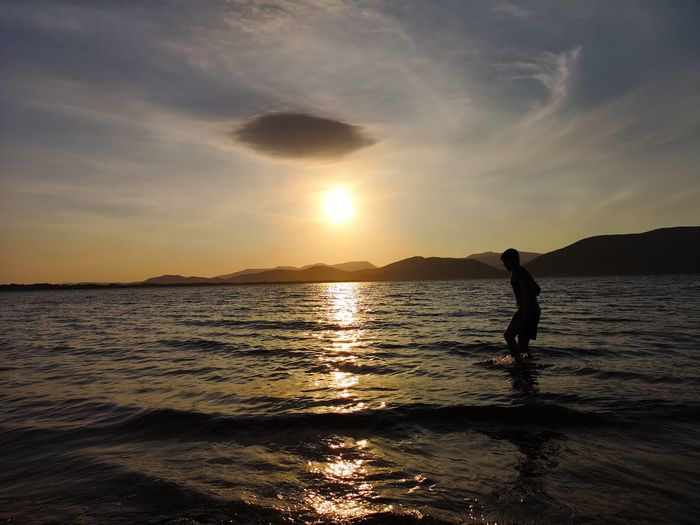 Silhouette boy wading in sea against sky during sunset