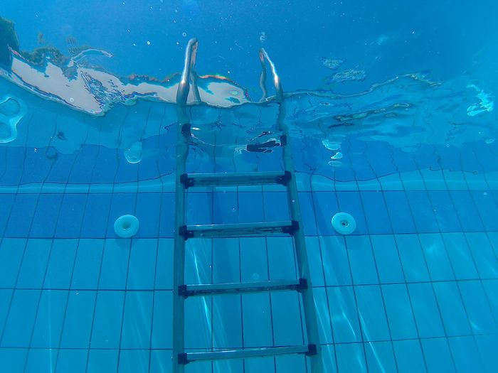 Low angle view of ladder in blue swimming pool
